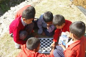 Guranse students enjoying ETC-supplied chess set