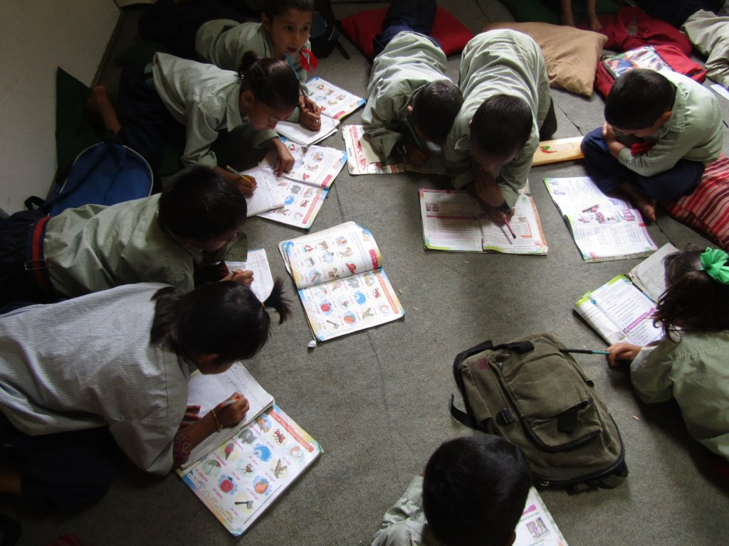 Jalpeshwori students writing in their workbooks