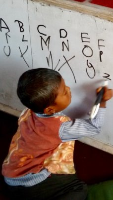 Boy practicing writing on ETC-provided white board