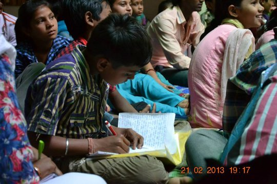 A child taking notes during the manifesto workshop