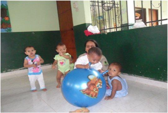 Babies playing with a caretaker at Pivijay Home