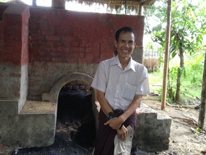Project Director with burned rice husks behind