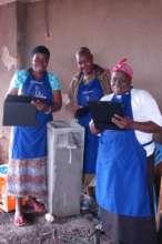 Women inspect the biosand filter for leaks
