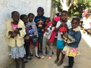 Children enjoying a new set of dolls