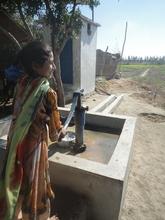 Noor Nisa's daughter with the water pump