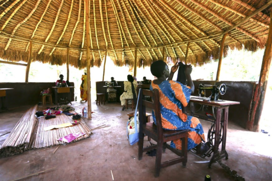 The women work in an outdoor thatched building.