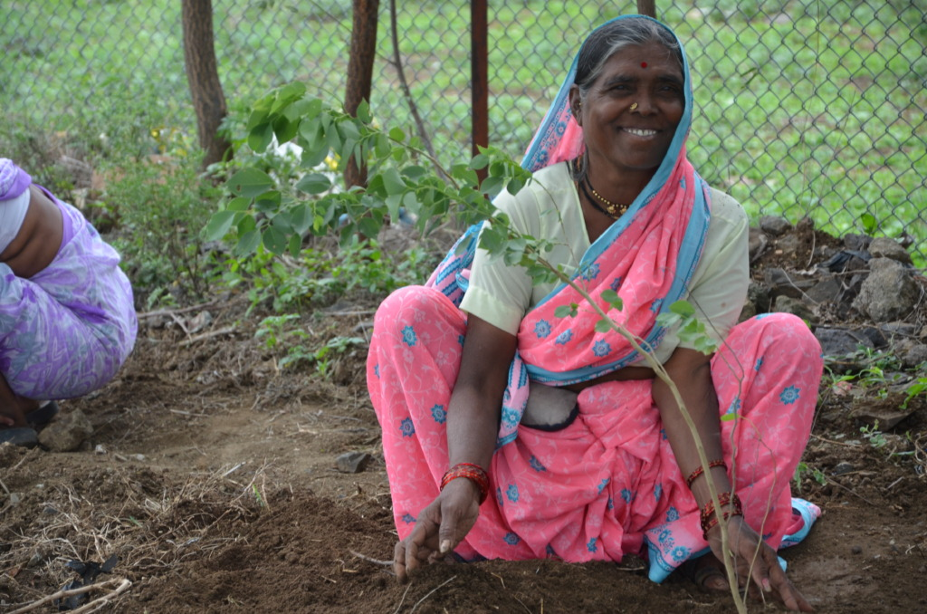 Village Health Worker planting a tree