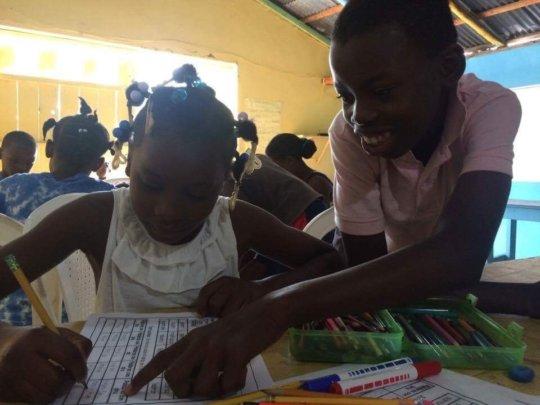 Kendi uses Creole to help his classmate, Yudelca.