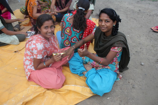 Adolescent girls applying henna art.