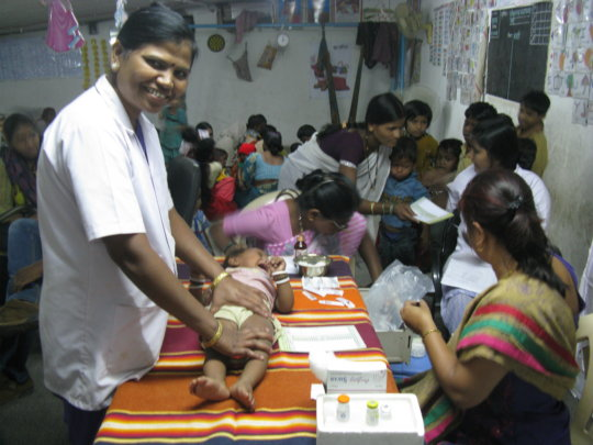 Nirmala assisting a baby's check up