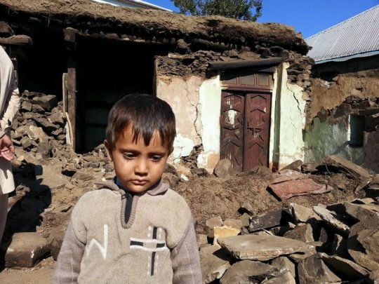 A Little Boys Stands In Front of His Damaged Home
