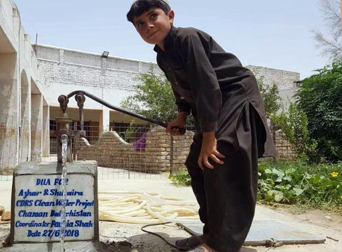 A young boy gets clean water from a new pump