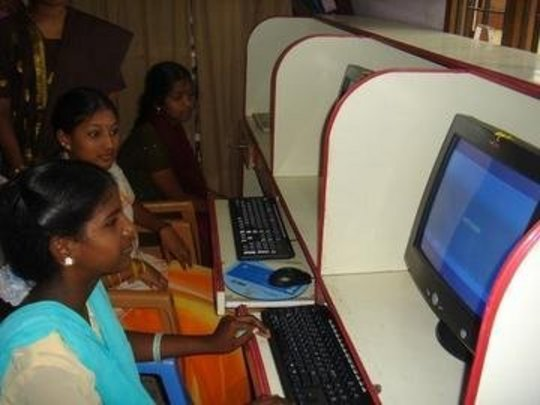 Adolescent girls learning computer skills