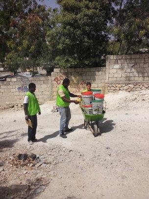SOIL's Sasha Kramer helping collect poo buckets!