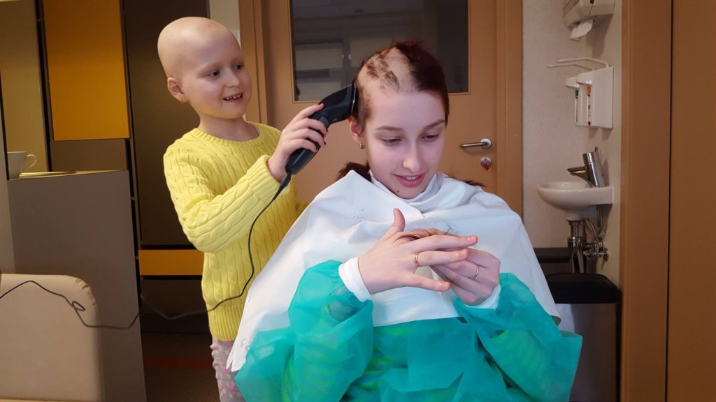 Meja cutting hair to her hospital ward friend