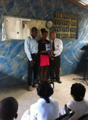 Milene receiving award with her father and teacher