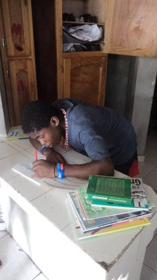 Ysaac writing his name on his school books