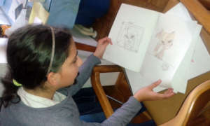 Ivana proudly shows a notebook of her drawings