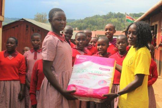 Joyce,HFAW, handing over sanitary to Pisgan girls