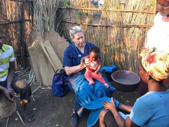 Dr. Lara examines a newborn at a homestead