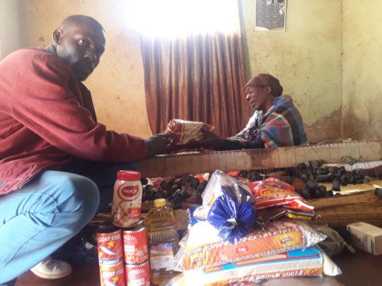 Pastor Bheki handing over food to a patient