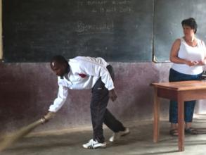 A teacher unusually sweeping the classroom floor