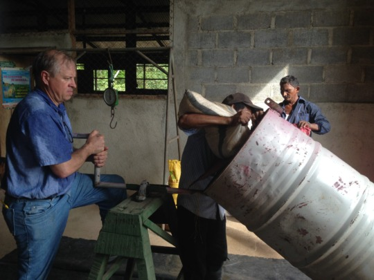 Pouring seed corn into barrel to be treated