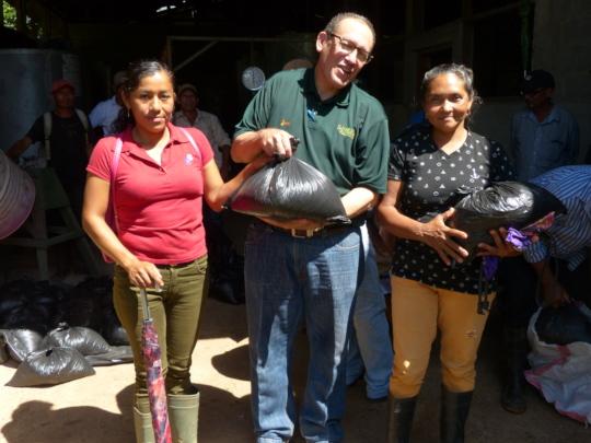 Jorge Campos hands out sacks to women farmers.