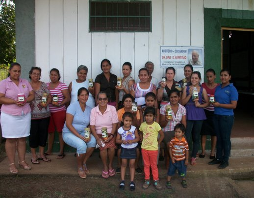Beneficiaries display their first jars of pickles.