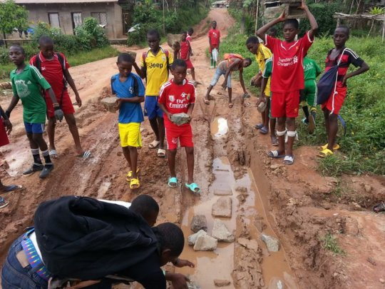 Youth placing stones in the road to improve access