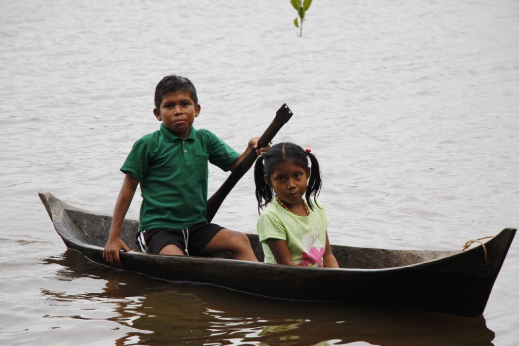 A boy brings his sister to clinic from far upriver