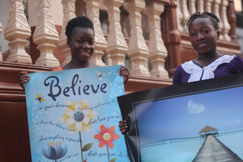 Dorcas and Geraldine - 2 orphans holding posters