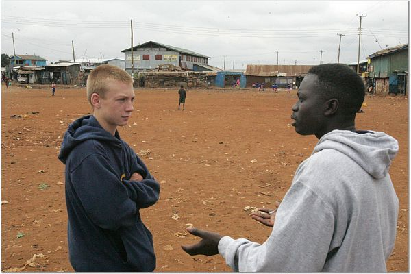 CFK Youth Sports Program Officer shows Kyle the practice field i