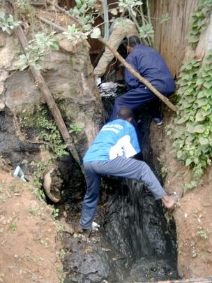 Taka ni Pato members unclog a drainage pipe