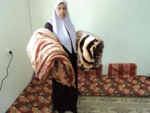 Mustafa's wife with blankets from kit.