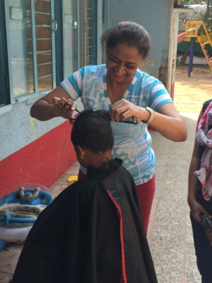 Volunteer helping in giving kids a hair cut