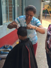 Volunteer helping in giving kids a hair cut