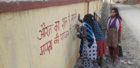 Women writing a pro-menstruation slogan
