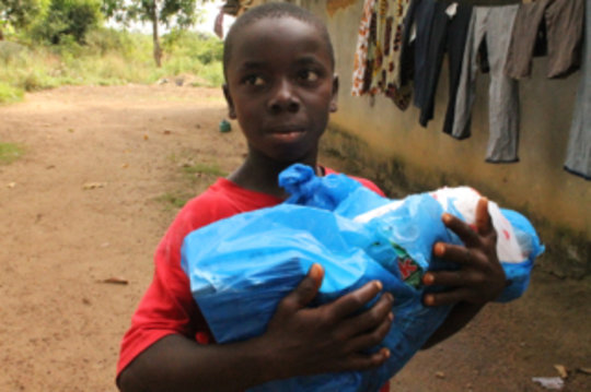 A survivor of Ebola carries a care package home