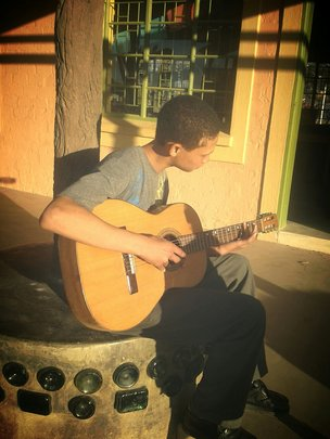 Lorenzo learning to play the guitar
