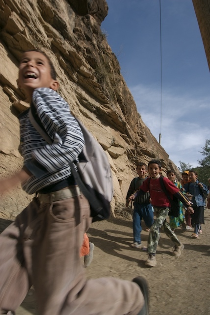 School children running to school.