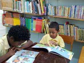 Zion reading in the Library with his classmate.