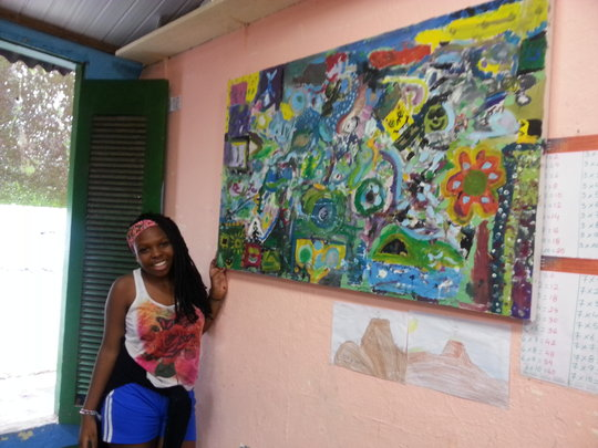 Paola and a painting created by the children