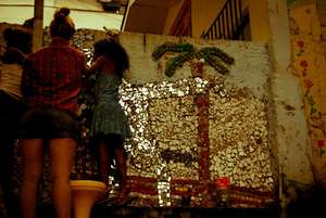 Volunteer with two girls doing mosaic