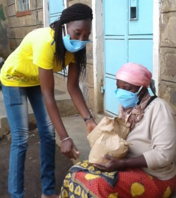 Our student giving food to an elderly granny