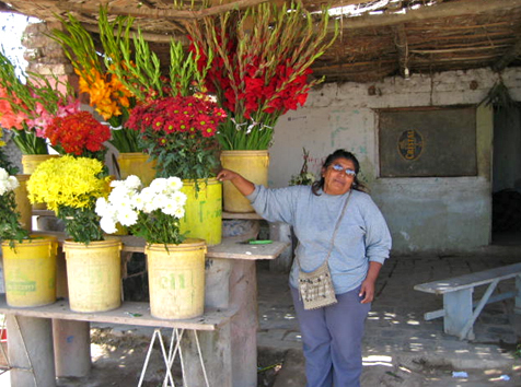 Selinita stands with her flower stand.
