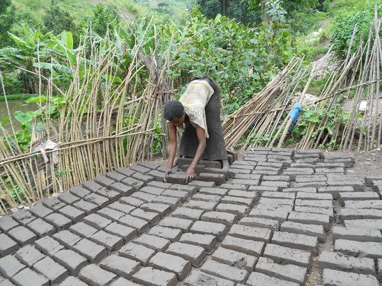 A parent arranging bricks for drying
