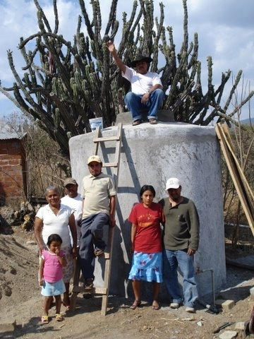 Jorge and his family proudly standing by the new rainwater stora