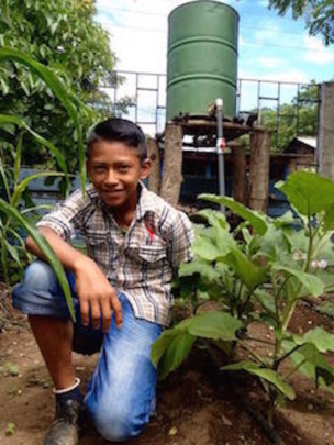Proud student in front of drip irrigation system
