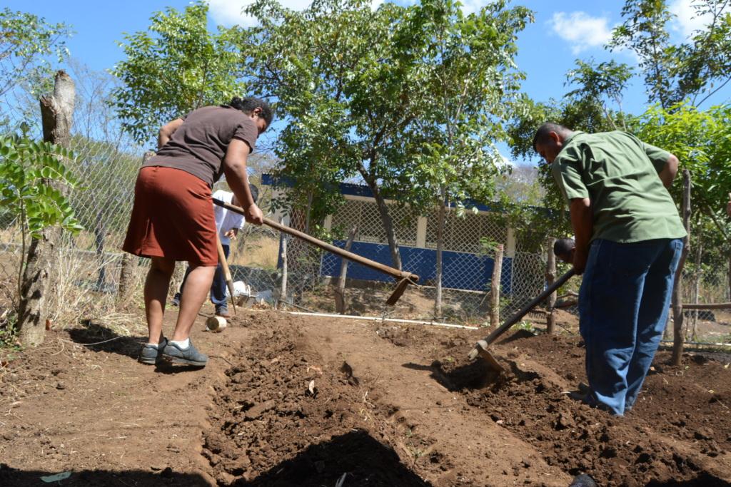 Parent and teacher preparing Candelaria soil